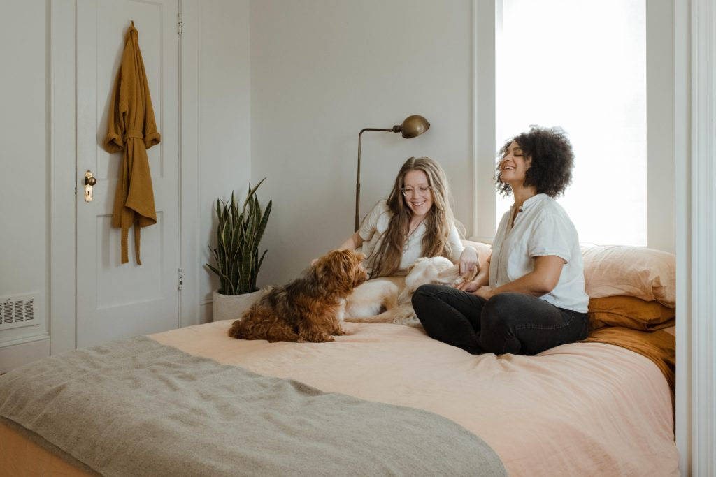 Celebrating childfree women | 2 women and a dog chatting on a bed